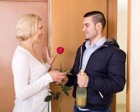liaison: Happy son with gifts visiting senior mother at her place Stock Photo