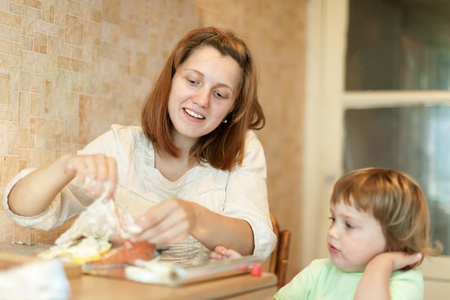 farcie: Woman with child cookis in the kitchen together