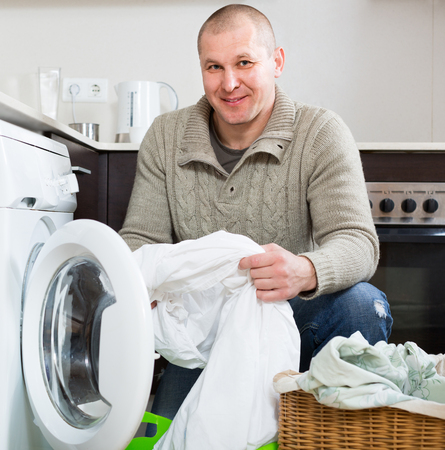 man laundry: Home laundry. Happy smiling man using washing machine at home