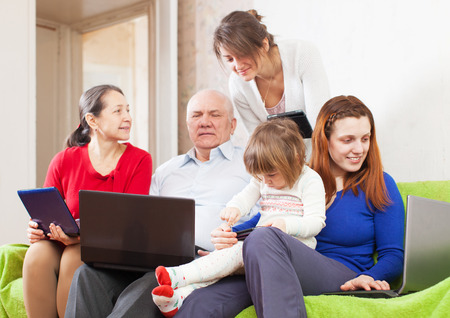 family  room: Happy multigenerations family   in  room with laptops Stock Photo