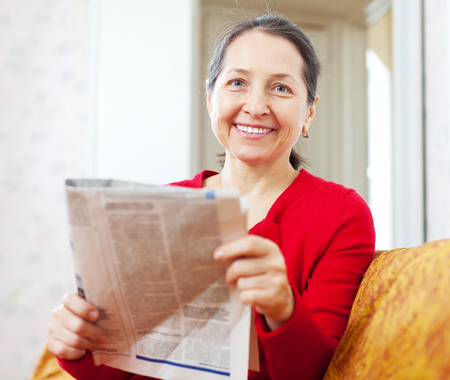 1 woman only: Joyful mature woman sits on sofa with newspaper