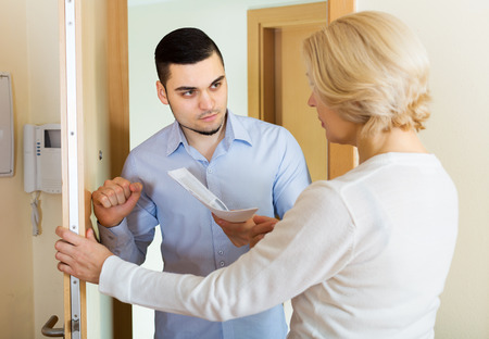 Young collector is trying to get the arrears from mature woman at home door