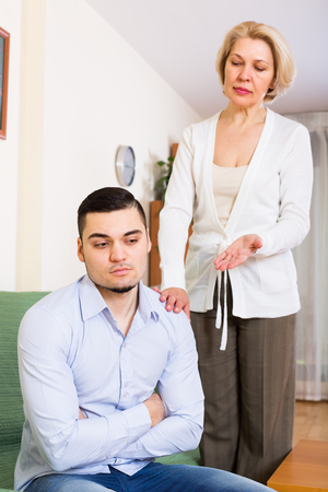 mismatch: Home conflict between mature woman and her sad young handsome boyfriend Stock Photo