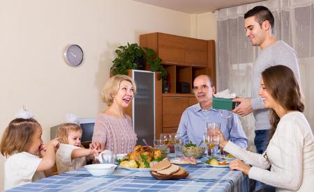 congratulating: Young man congratulating heartily family member at home