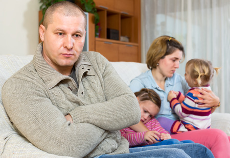 father and children: Wife cant forgive his husband. Man is sitting on a sofa on the front and his family is sitting behind him. Two crying daughters and a dissapointed wife