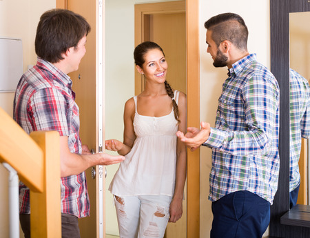 inviting: american family couple inviting friend in the apartment Stock Photo