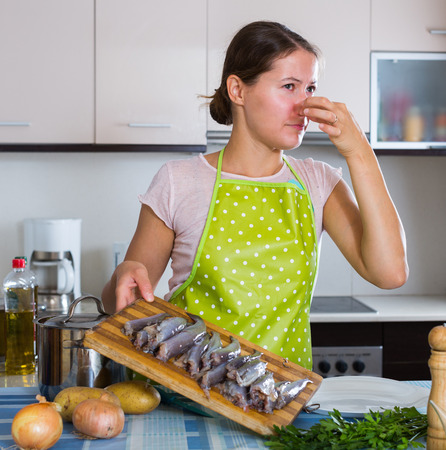 the stinking: Housewife in apron cooking fish and wincing of disgusting smell Stock Photo