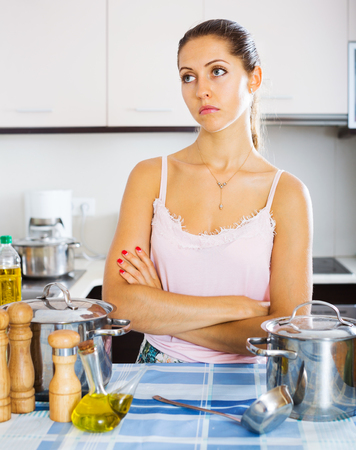 dispirited: Tired young woman standing at kitchen table