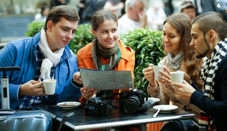 group search: adult european tourists drinking coffee at cafe and reading city map