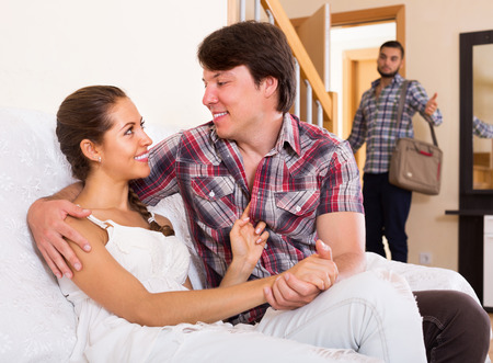 coming home: Surprised young husband coming home in wrong moment Stock Photo