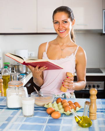 whisking: young woman whisking eggs for omelette at kitchen table