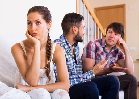 polygamy: Sad brunette girl and two men at home: problems of love triangle. Selective focus
