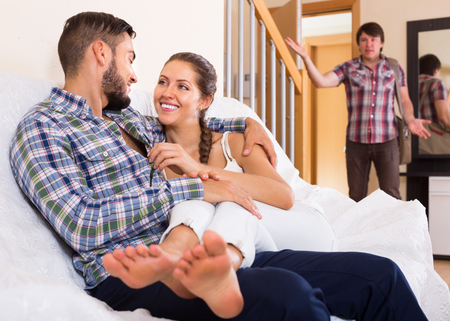 coming home: cheating young spouse coming home in wrong moment Stock Photo