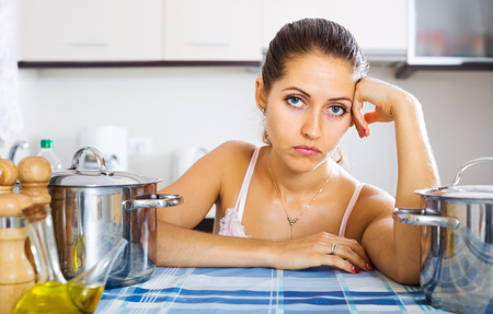 in low spirits: Tired young woman sitting at kitchen table