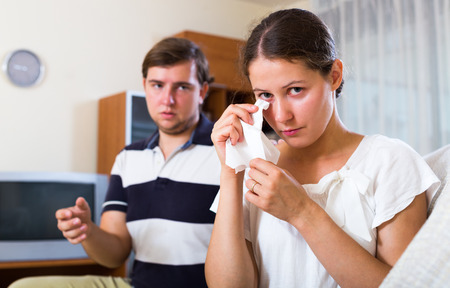 remit: Man trying reconcile with wife after bad argument in living room Stock Photo
