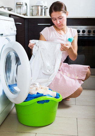 unwashed: Unhappy young woman with dirty white shirt near washing machine