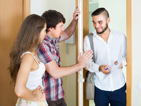 lurid: Bleak couple greeting cheerful young salesman in doorway