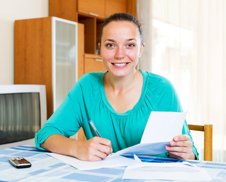 filling out: Positive girl filling out tax forms while sitting at her desk Stock Photo