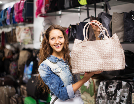 leather bag: Young woman choosing leather bag in shop Stock Photo