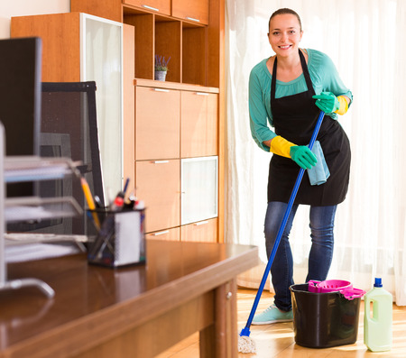 household tasks: Young woman cleaning the floor at office room