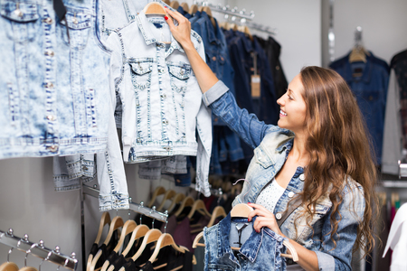coatee: Smiling woman selecting waistcoat at the commercial centre Stock Photo