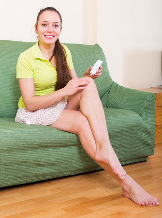 liniment: Smiling woman sitting with treatment for injury at domestic interior Stock Photo