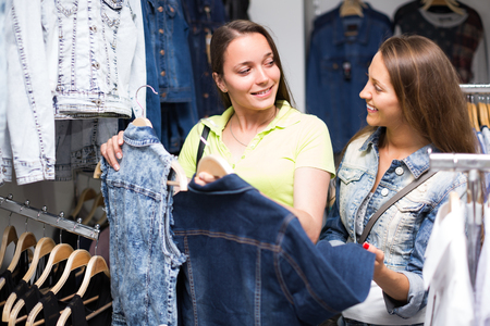 denim jacket: Two positive young smiling women choosing denim jacket in shop Stock Photo