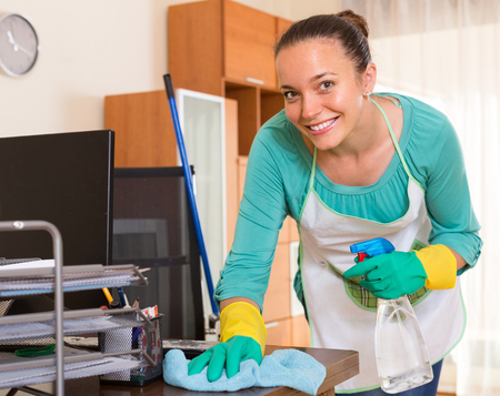 trabajando en casa: Smiling female professional cleaner making cleaning in the office-room Foto de archivo