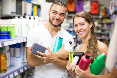 vend: Smiling young couple buying detergents, shampoo and perfume in supermarket. Selective focus