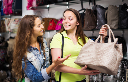 leather bag: Two happy women choosing leather bag in shop Stock Photo