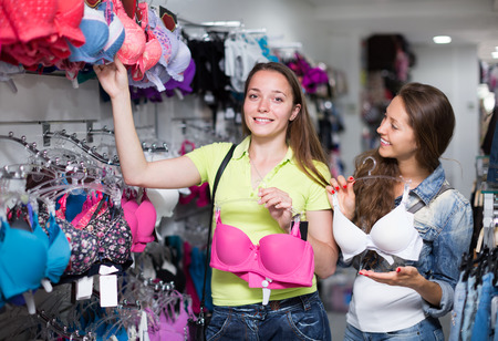 brassiere: Young attractive woman buying the brassiere in the clothing store