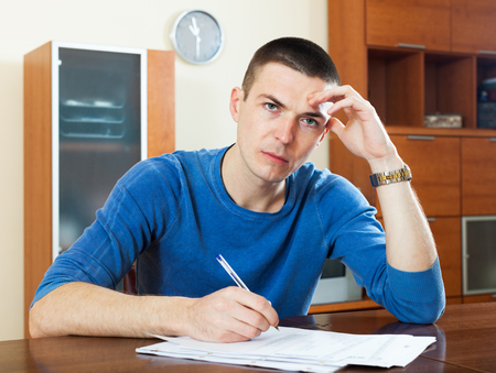 parsimony: Sad frustrated guy sitting at table filling out paperwork Stock Photo