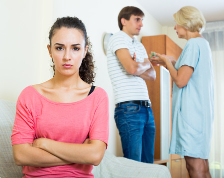 squabble: Frustrated young woman taking hard argue between husband and mother