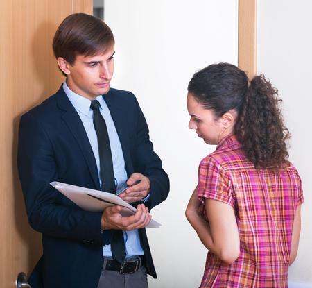 broken contract: Debts collector and poor woman standing in doorway of apartment Stock Photo
