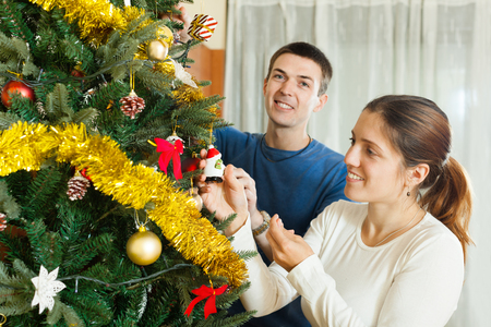 Smiling couple decorating Christmas tree in home interior Stock Photo