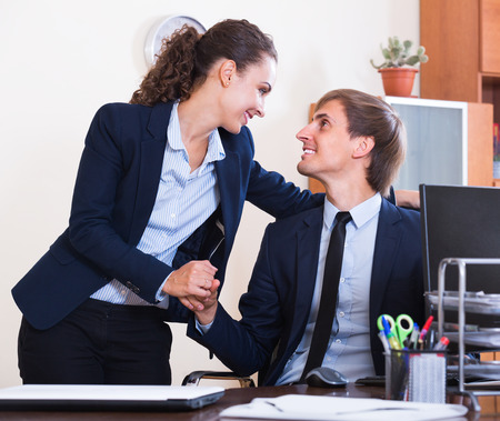 the tempter: Sexual harassment in office: young woman flirting with employee and smiling