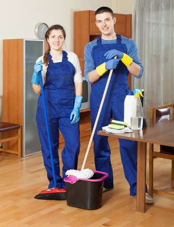 company premises: Two adult cleaners cleaning floor in room Stock Photo