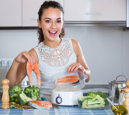 corcovado: Happy young brunette woman steaming salmon and vegetables in domestic kitchen