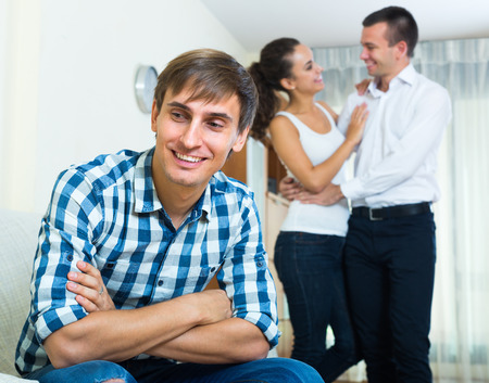 envious: Young guy in love triangle: his beloved woman prefers rival Stock Photo