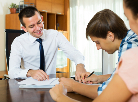 mortgage: Young family couple and positive banking agent discussing possibility of mortgage