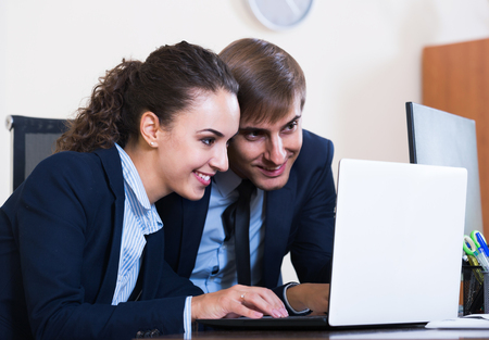 yuppie: Two young positive american managers using laptop at work in office