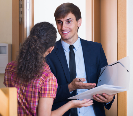 householder: happy spanish commercial agent greeting householder and selling subscriptions in hall