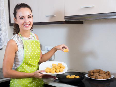 crocchette: Cheerful girl frying delicious crocchette in pan at home Stock Photo