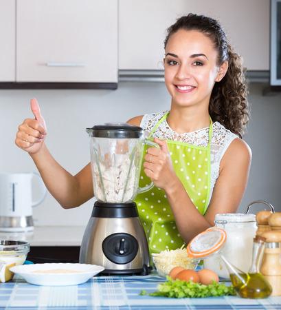 liquidiser: Happy girl using blender and grinding ingredients delicatessen