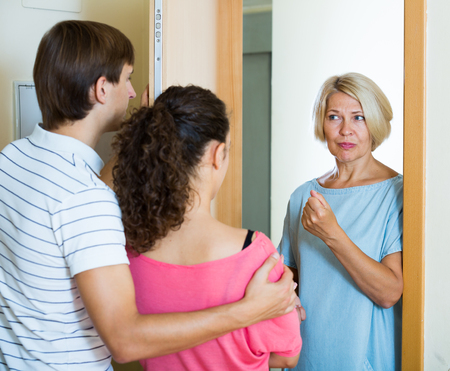 squabble: Young family couple arguing with mature woman at entrance Stock Photo