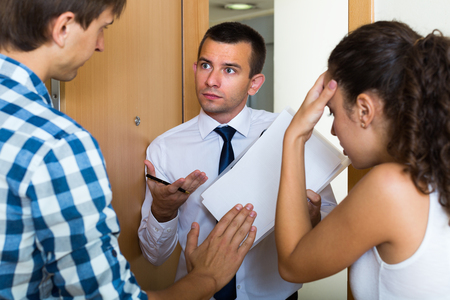 spouses: Debt collector and sad young spouses with overdue payment at the doorway