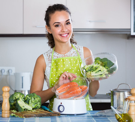 jorobado: Happy smiling adult girl steaming salmon and vegetables in domestic kitchen