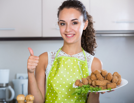 crocchette: Happy young woman posing with plate of deep-fried kroketten