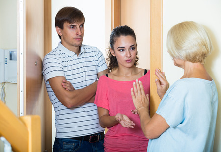 neighbours: Upset mature woman and couple of angry neighbours at doorway