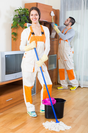 houseman: Cleaning premises team with equipment working at clients home. Focus on girl